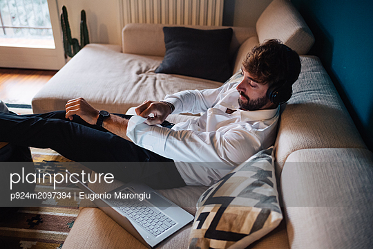Mid adult man reclining on sofa listening to headphones while rolling up sleeves - p924m2097394 by Eugenio Marongiu