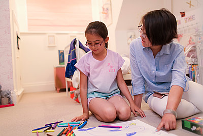 Mother and daughter coloring on bedroom floor - p1023m2033934 by Sam Edwards