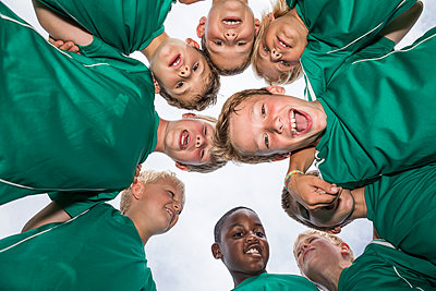 Happy young football players huddling - p300m1580817 by Fotoagentur WESTEND61