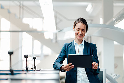 Female business professional using digital tablet in industry - p300m2300294 by Kniel Synnatzschke