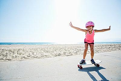 Girl riding skateboard at beach - p555m1305539 by Peathegee Inc