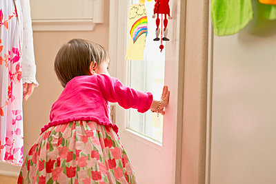 Hispanic girl looking out door - p555m1479576 by Sollina Images