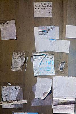 Torn stickers on a wall - p9246736f by Image Source