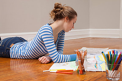Girl lying on floor drawing picture - p924m805880f by davidgoldmanphoto