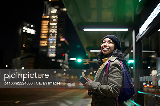 smiling woman standing using his cellphone at the bus station - p1166m2224538 by Cavan Images