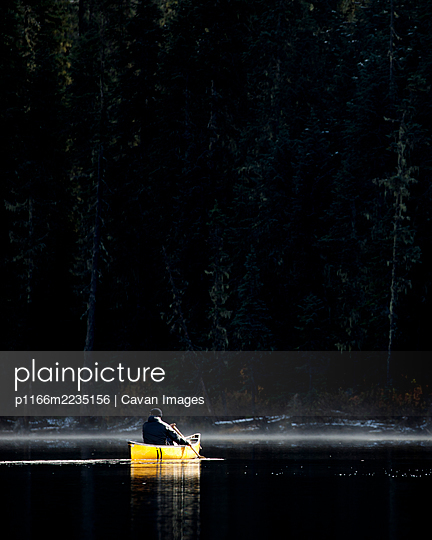 Rugged adventurer solo paddles canoe on misty calm lake by thick forest - p1166m2235156 by Cavan Images