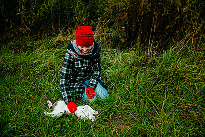 Girl Smiling as she Pets Her Cats Stomach Outdoors in the Grass - p1166m2153341 by Cavan Images