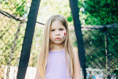 Unhappy young girl standing on a trampoline between the netting - p1166m2208059 by Cavan Images