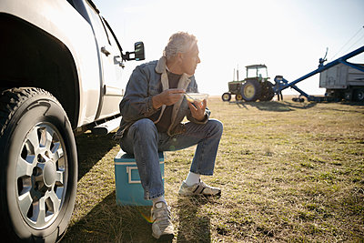 Male farmer eating lunch, taking a break on sunny farm - p1192m2040219 by Hero Images