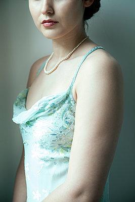 Junge Frau mit Perlenkette im Trägerkleid - p1248m2270283 von miguel sobreira