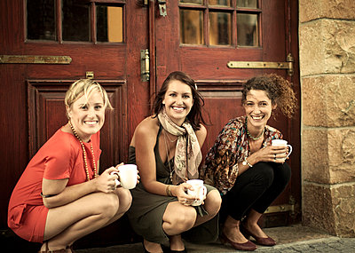 Young women with coffee cup smiling while crouching against door - p300m2264522 by LOUIS CHRISTIAN