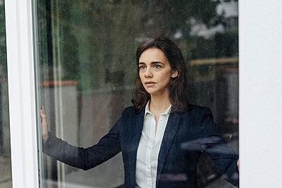Geschäftsfrau blickt aus dem Fenster - p586m1510781 von Kniel Synnatzschke