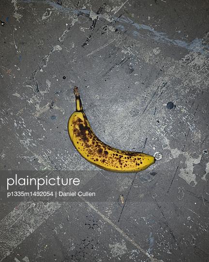 Banana on concrete floor - p1335m1492054 by Daniel Cullen