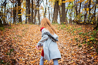 Young Red Hair Girl Playing Outside in Fall Leaves - p1166m2147093 by Cavan Images