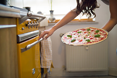 Young woman holding homemade pizza with mozzarella, chili peppers and basil - p300m1069005f by Richárd Bellevue
