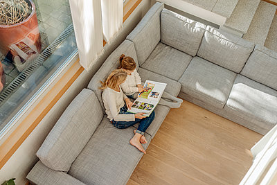 Mature woman and girl at home looking at photo album on couch - p300m1459730 by Joseffson