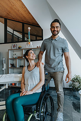 Smiling physiotherapist with female patient sitting on wheelchair - p300m2275989 by Mareen Fischinger