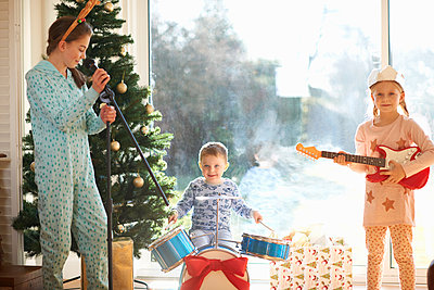 Boy and sisters playing toy drum kit and guitar on christmas day - p429m1226801 by Peter Muller