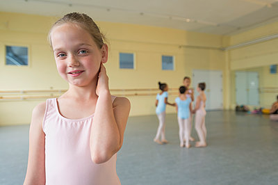 Portrait of smiling girl in ballet studio - p555m1491106 by Mark Edward Atkinson