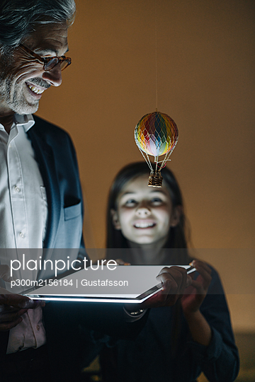Happy senior buisinessman and girl with hot-air balloon and shining tablet in office - p300m2156184 by Gustafsson