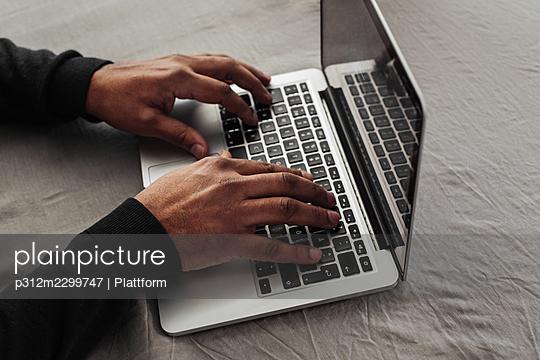 Man's hands on laptop keyboard - p312m2299747 by Plattform