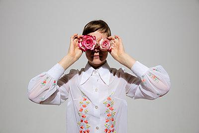 Junge Frau hält sich Rosen vor den Augen - p1212m1092909 von harry + lidy