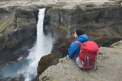 Hiker with backpack on cliff by Haifoss waterfall in Iceland - p1427m2077621 by Oleksii Karamanov