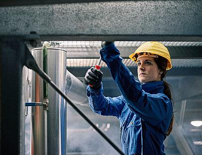 Craftswoman wearing hard hat at work - p300m1549944 by Christian Vorhofer