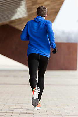 Rear view of jogger running on a street - p300m2140784 by Josep Suria