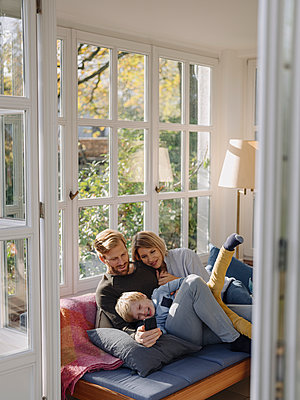 Happy family using cell phone in sunroom at home - p300m2205487 by Kniel Synnatzschke