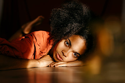Afro young woman lying on floor at home - p300m2267431 by Tania Cervián