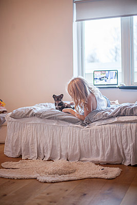 Girl with puppy lying down on bed - p312m1121625f by Christina Strehlow