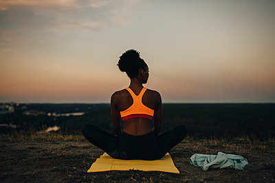 Rear view of sportswoman sitting on exercise mat during sunset - p426m2270555 by Maskot