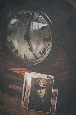 Stapel alter Fotos eines jungen Soldaten an eine Uhr gelehnt - p946m938936 von Maren Becker