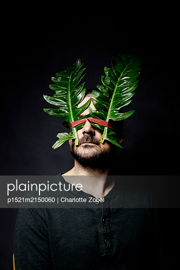 Man with big leaves on the face - p1521m2150060 by Charlotte Zobel