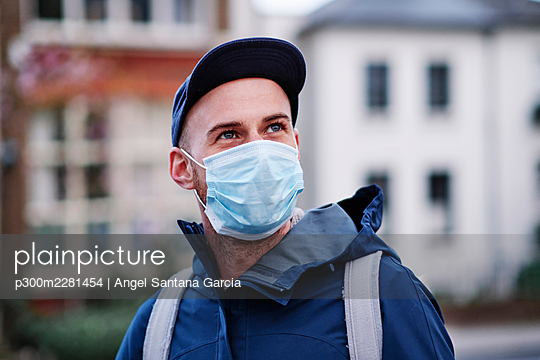 Man with gray eyes looking away while wearing protective face mask during pandemic - p300m2281454 by Angel Santana Garcia
