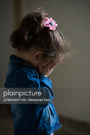 Trauriges kleines Mädchen mit Händen vor dem Gesicht - p794m2031105 von Mohamad Itani