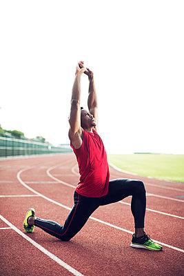 Full length of male athlete exercising on running tracks against clear sky - p1166m1088130f by John Trice