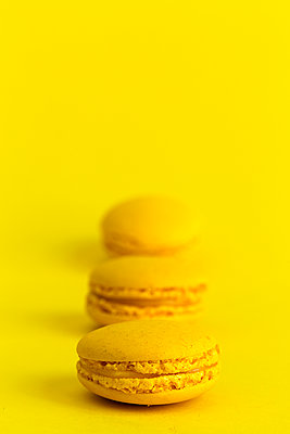 Close-up of macaroons in row over yellow background - p1166m2008975 by Cavan Images
