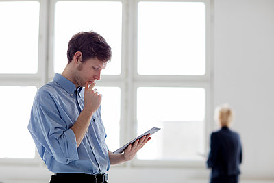 Junger Mann im Büro mit Ipad - Kollegin im Hintergrund - p1212m1115608 von harry + lidy