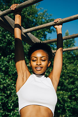 Female athlete looking down while hanging on monkey bar in park - p426m2270604 by Maskot