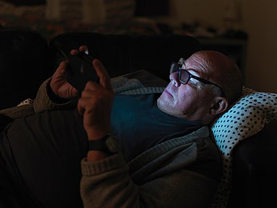 Mature man, lying on sofa, using smartphone, at night, face illuminated - p429m1052733 by Elke Meitzel