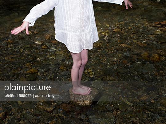 Mädchen steht auf einem Stein im Wasser - p945m1589073 von aurelia frey