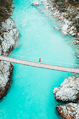 Aerial shot of young woman standing on bridge above whitewater river - p1166m2153633 by Cavan Images