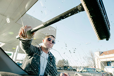 Man Washing Car Window at Gas Station - p1262m1194765 by Maryanne Gobble