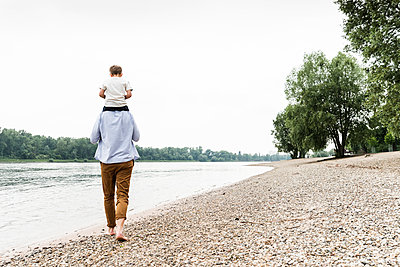 Father carrying son on shoulders at the riverside - p300m2005345 von Uwe Umstätter