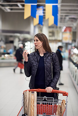 Woman talking on mobile phone through headphones while standing with shopping cart at supermarket - p426m1451858 by Maskot