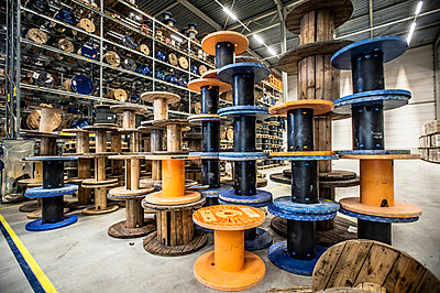 Empty cable drums stacked in warehouse - p429m803061f by Arno Masse