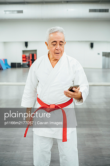 senior Karate master using mobile cell phone - p1166m2177057 by Cavan Images