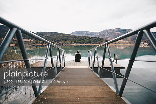 Back view of young woman sitting on jetty at lake - p300m1581314 von Oriol Castelló Arroyo